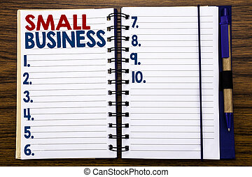 Writing text showing Small Business. Business concept for Family Owned Company Written on notebook note paper, wooden background with pen and marker.
