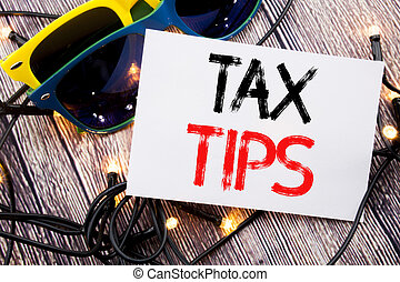 Writing text showing Tax Tips. Business concept for Tip Forn Taxes written on sticky note with copy space on old wood wooden background with sunglasses
