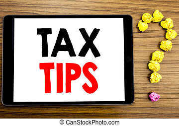Writing text showing Tax Tips. Business concept for Tip Forn Taxes written on tablet computer on the wooden background with question mark made of folded paper.