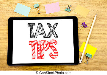 Writing text showing Tax Tips. Business concept for Tip Forn Taxes Written on tablet laptop, wooden background with sticky note and pen