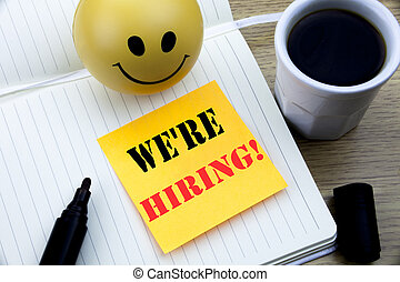 Writing text showing We Are Hiring Now. Business concept for Recruitment Human Resources written sticky note empty paper, Wooden background with copy space, Coffee and marker