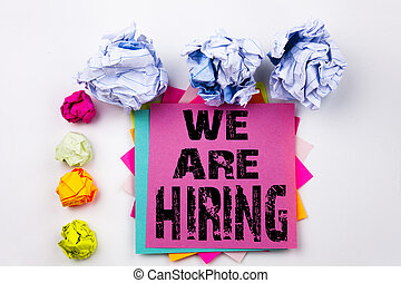 Writing text showing We Are Hiring written on sticky note in office with screw paper balls. Business concept for Recruitment and Job recruiting advertisement on the white isolated background.