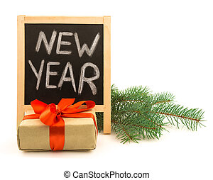 Written New Year on a blackboard, Christmas twig and gift with red ribbon