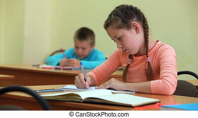 Written task - Little girl fulfilling written tasks in...