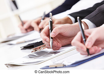 Written work - Close-up of business person hand working with...