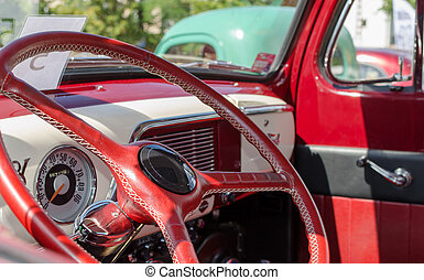 WROCLAW, POLAND - August 11, 2019: USA cars show: 1951 Renovated Ford F-100 Pickup Truck of red and white colors. Close-up of inside dashboard and steering wheel.