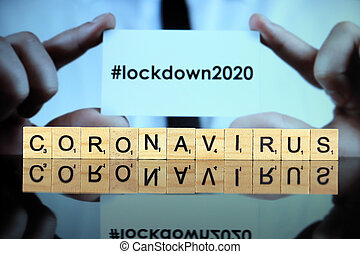 WROCLAW, POLAND - MARCH 30, 2020: The word CORONAVIRUS made of wooden letters, and man holding a business card with the word LOCKDOWN (with hashtag, popular on social media) in the background.