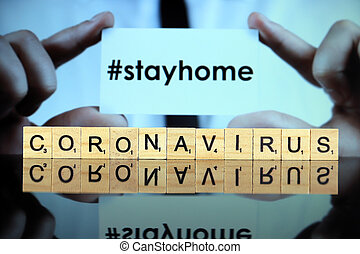 WROCLAW, POLAND - MARCH 30, 2020: The word CORONAVIRUS made of wooden letters, and man holding a business card with the words STAY HOME (with hashtag, popular on social media) in the background.