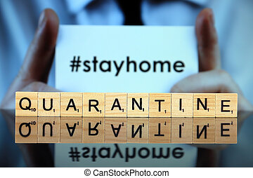 WROCLAW, POLAND - MARCH 30, 2020: The word QUARANTINE made of wooden letters, and man holding a business card with the words STAY HOME (with hashtag, popular on social media) in the background.