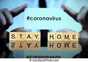 WROCLAW, POLAND - MARCH 30, 2020: The words STAY HOME made of wooden letters, and man holding a business card with the word CORONAVIRUS (with hashtag, popular on social media) in the background.