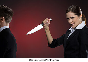 Wrong business partner. Smiling young woman in formalwear holding a knife near man in suit standing back to her