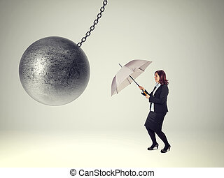 wrong solution - businesswoman with umbrella and heavy iron...