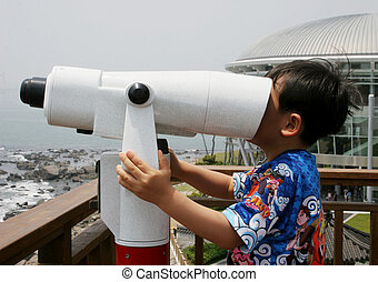 Wrong way - Young boy looking in a telescope at the sea the...