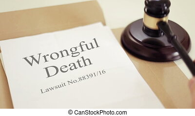 Wrongful death lawsuit documents with gavel placed on desk of judge in court