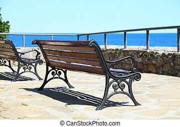 Wrought-iron bench on a stone seafront.