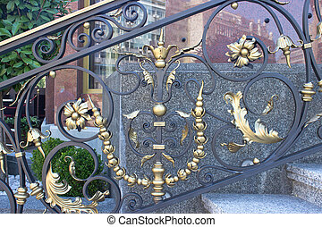 Wrought iron fence with golden ornaments