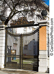 Wrought iron gates - In front of closed wrought iron gates,...