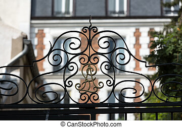 Wrought iron railing in symmetrical pattern on top of a gate