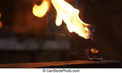 Wrought rose is put on a steel anvil covered with flame in a...