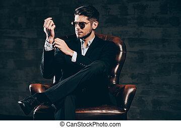 wszystko, musieć, czuć się, perfect.young, przystojny, człowiek, w, garnitur, i, sunglasses, regulując, rękaw, na, jego, koszula, znowu, posiedzenie, w, skórzane krzesło, przeciw, ciemny, szary, tło