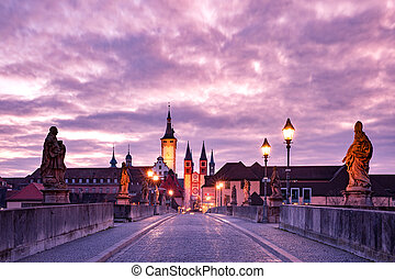 Old Main Bridge, Alte Mainbrucke with statues of saints, Cathedral and City Hall in Old Town at pink sunset, Wurzburg, Bavaria, Germany