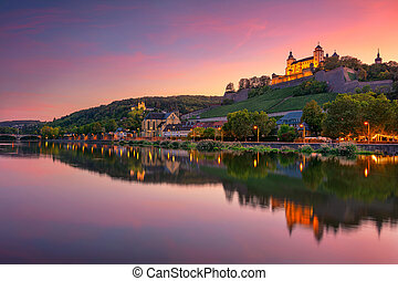 Cityscape image of Wurzburg with Marienberg Fortress and reflection of the city in Main Rive during beautiful sunset.