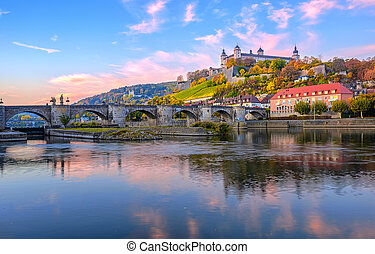 Wurzburg, Bavaria, Germany, view of the Marienberg Fortress and the Old Main Bridge reflecting in river on colorful sunrise