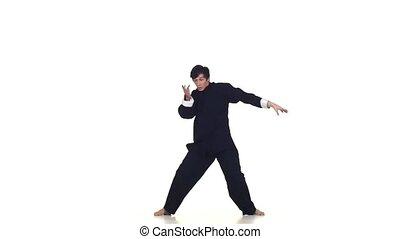 Wushu or karate man in sportswear performing a kick. Martial arts, Slow motion