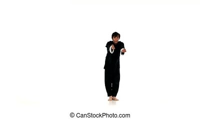 young wushu or karate man jumping, high kick and fist punch, Isolated on white background, a black clother and belt. wushu, kungfu, sambo, aikido