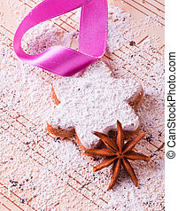 X-mas cookie with a pink bow and icing sugar and one anise