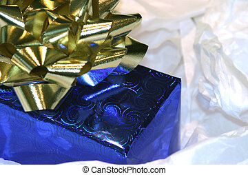 X-mas gift wrapped in in silver blue paper and finished with a gold bow sits isolated on a white background of crumpled white tissue paper lit up with above right sunlight