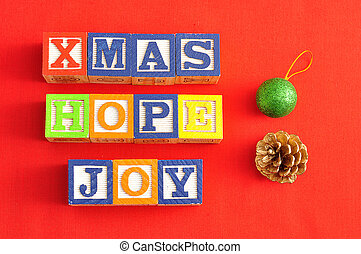 Xmas, Hope and Joy spelled with Alphabet blocks and an acorn and bauble on a red background