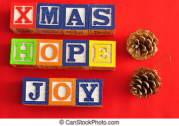 Xmas, Hope and Joy spelled with Alphabet blocks and two acorns on a red background
