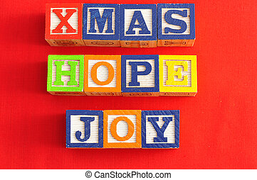 Xmas, Hope and Joy spelled with Alphabet blocks on a red background