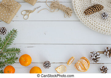 Xmas, merry christmas frame from decorations, fir cones and branch, knitted scarf, gift box, orange mandarin on white wooden planks table Top view. Trendy hand mande design mockup. New year background.
