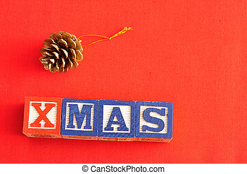 Xmas spelled with Alphabet blocks and an acorn christmas tree decoration on a red background