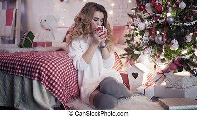Xmas - Young beautiful woman drinks tea near a Christmas tree