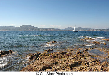 Yacht and rocks St Tropez, with St Maxime in the distance.