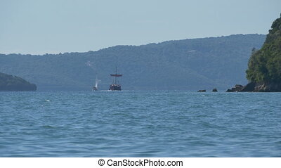Yacht and Ship near Greek Island - A yacht and wooden...