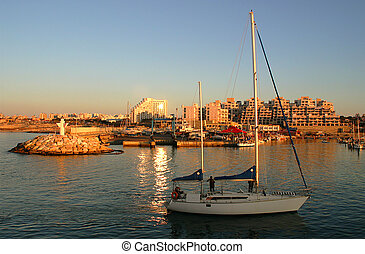 Yacht entering marina at sunset. - Yacht entering marina at...