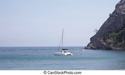 yacht in bay against the backdrop of sea and rocks