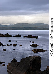 scenic view in kerry ireland of lone yacht sailing in rocks and sea with mountains against a beautiful cloudy sky