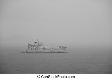 Yacht on the ocean in the foggy day in black and white tone