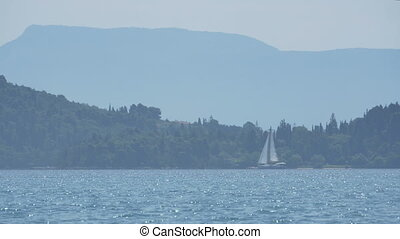 Yacht Passing near Shore - Sailboat travelling at the...