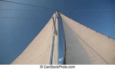 yacht sailboat developing in the wind on blue sky background