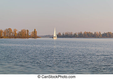 Yacht, Sailboat in the river goes on the water autumn landscape