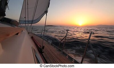 Yacht sailing against sunset. (HD)