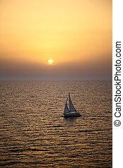 Yacht sailing at sunset