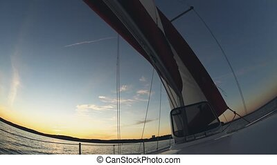 Yacht sailing in open water. Sail waves in wind, boat goes through water. Beautiful water landscape on sunset. Close-up view of sailboat.