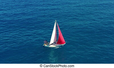 Yacht sailing on open sea at sunny day. Sailing boat with a red sail.